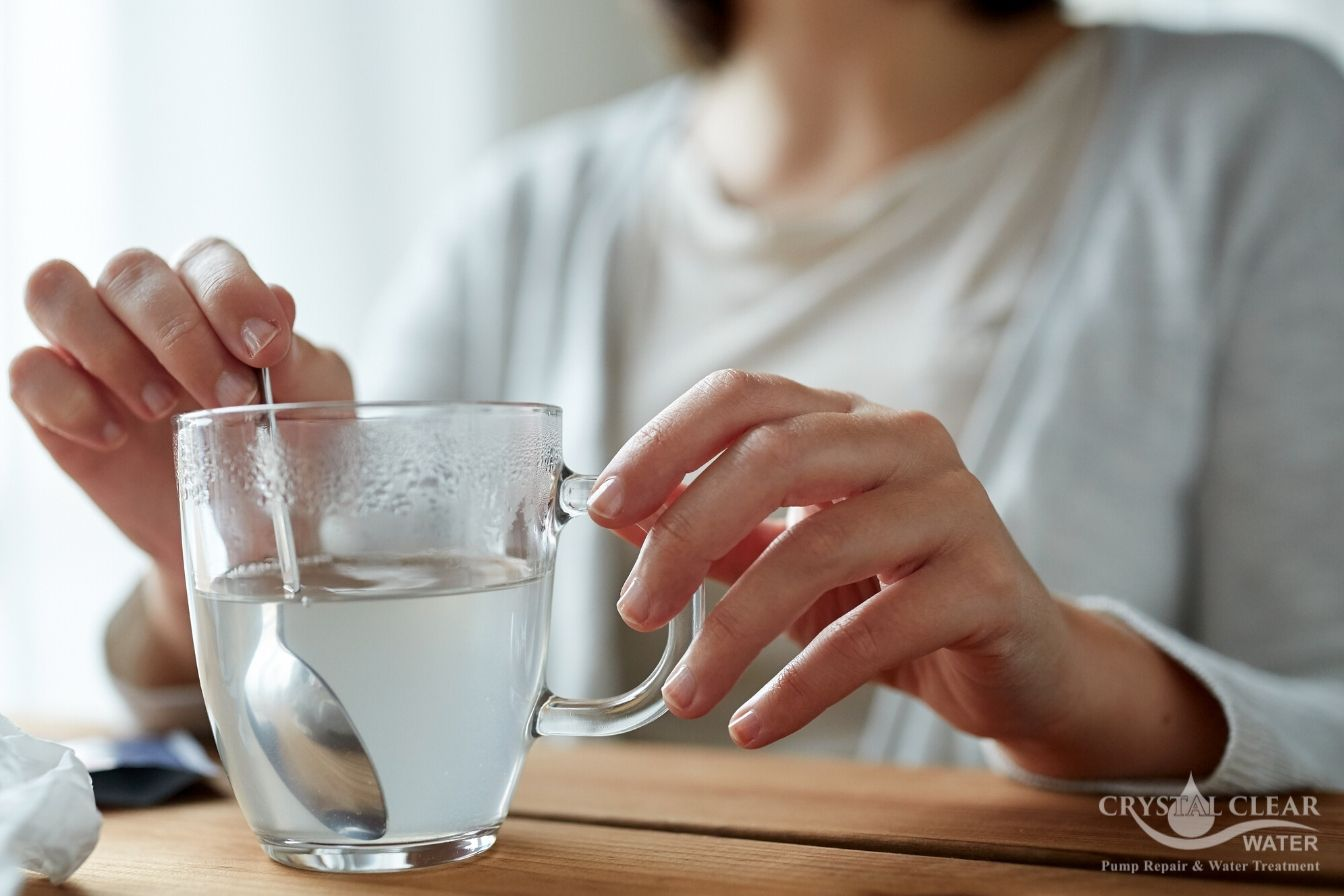 Woman stirring glass of water tds
